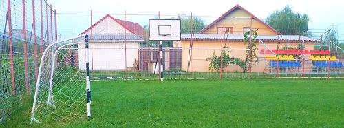"""Sportplatz Verseni. Hintendran das """"Schweizer Haus"""" (ein Magazin, links), der """"Club"""" (Mitte) und das eine der zwei renovierten """"Vile"""" (hinten)."""